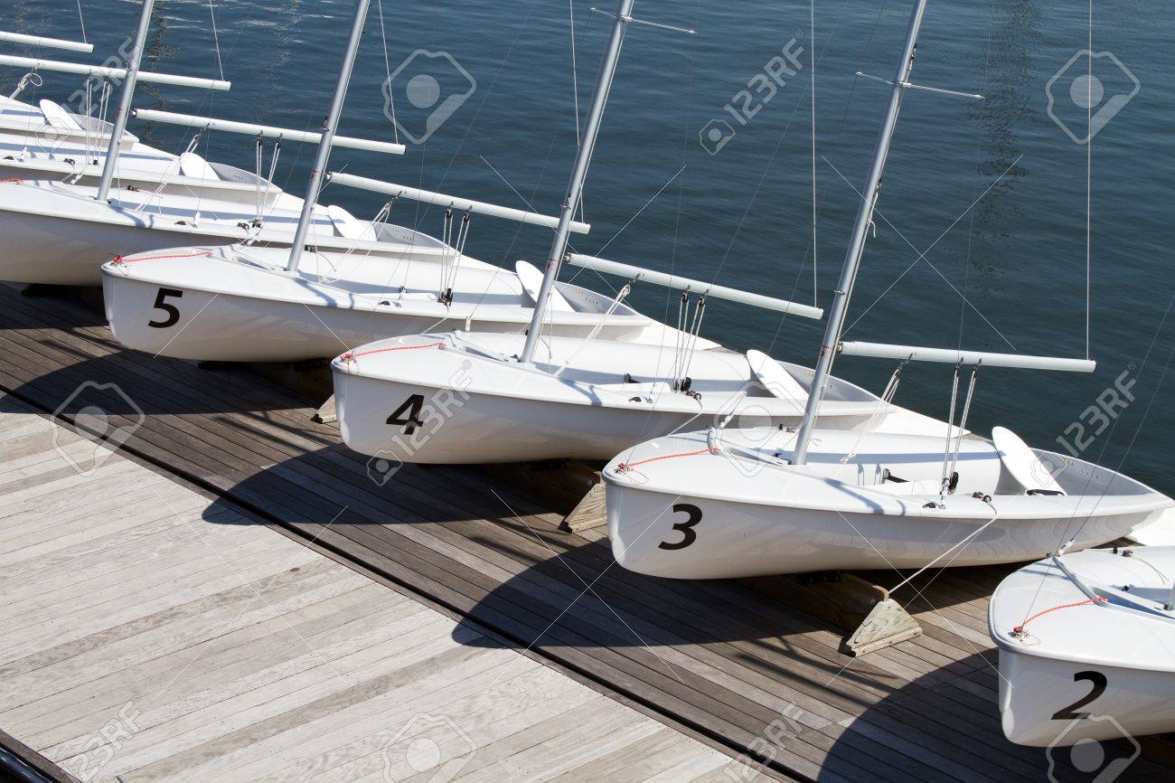 Small rental centerboard sailboats line the pier at a yacht club