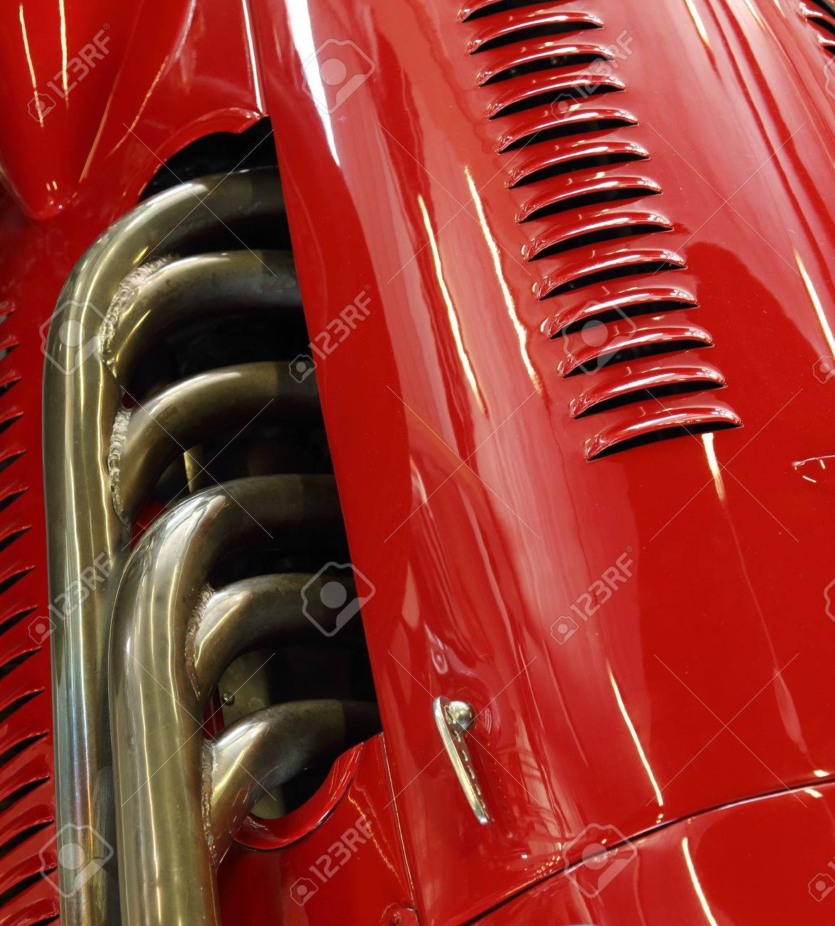 closeup of the exhaust and bodywork of a red classic racing car