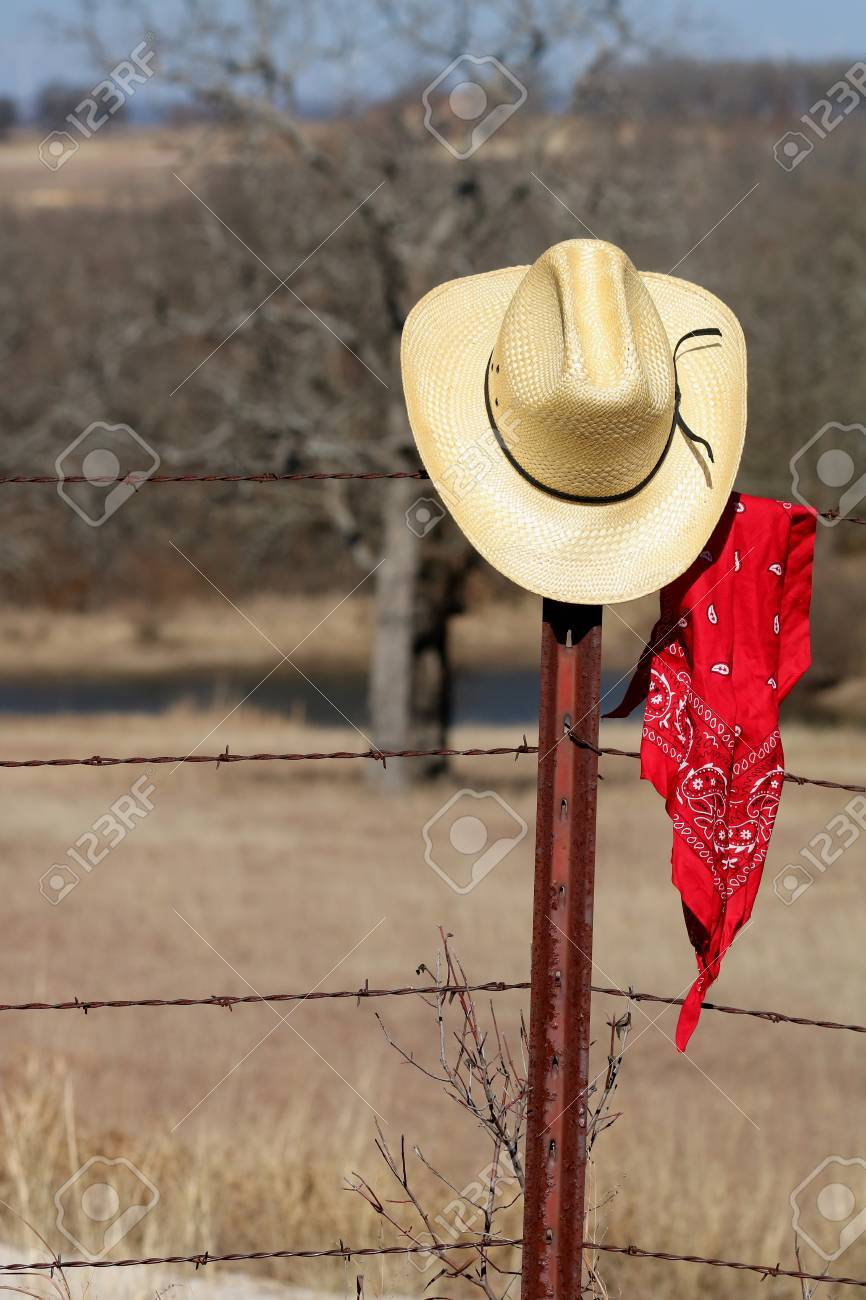 Stock Photo - Yellow straw cowboy hat and red bandana hanging on the fence  post of a rusty barbed wire fence with field and trees in the background. 892df116e08