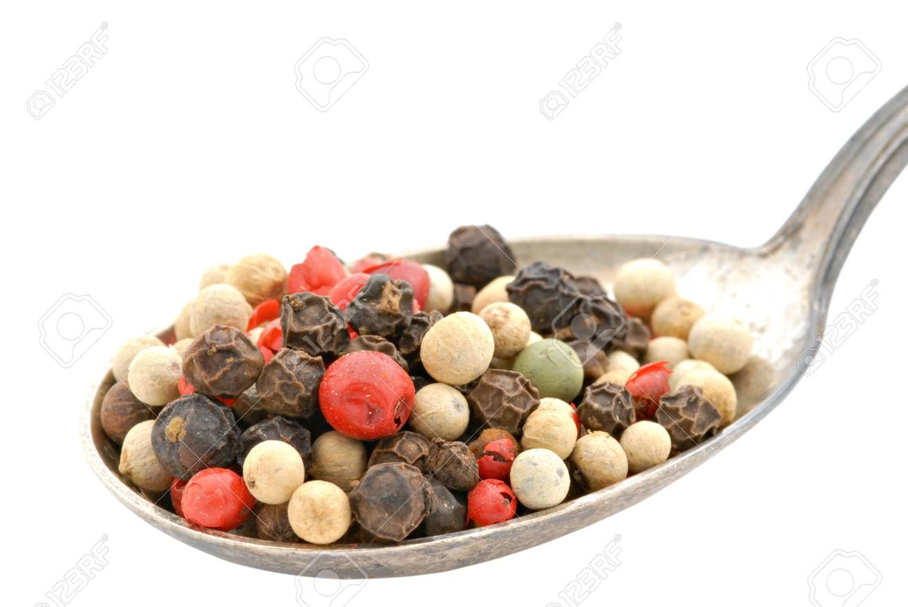 A spoonful of colorful peppercorns in a tarnished spoon. Stock Photo - 3245386
