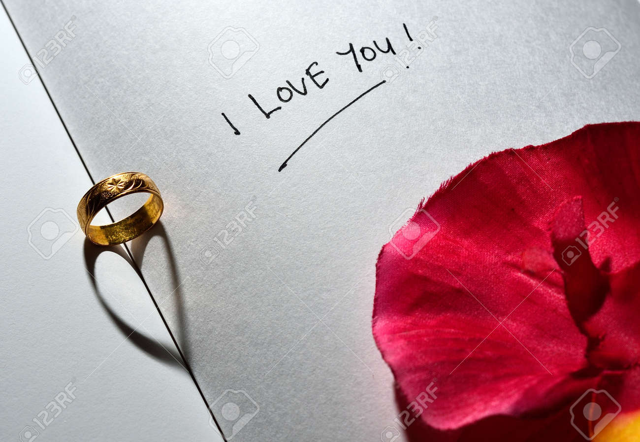 Ring with heart shadow and I love you text with rose on white plain book Stock Photo - 19178523