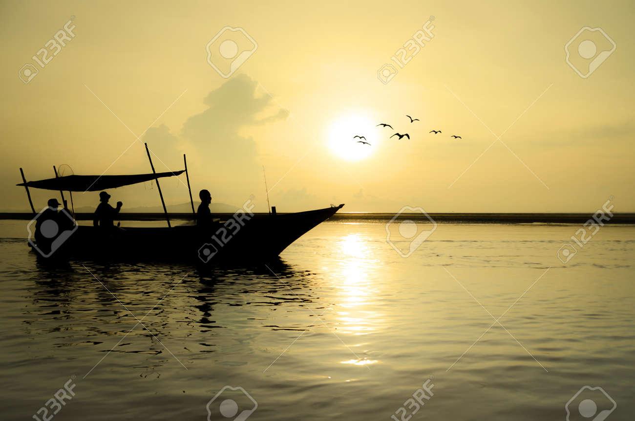 Fishing Boat at Sunrise with bird flying around Stock Photo - 20180063