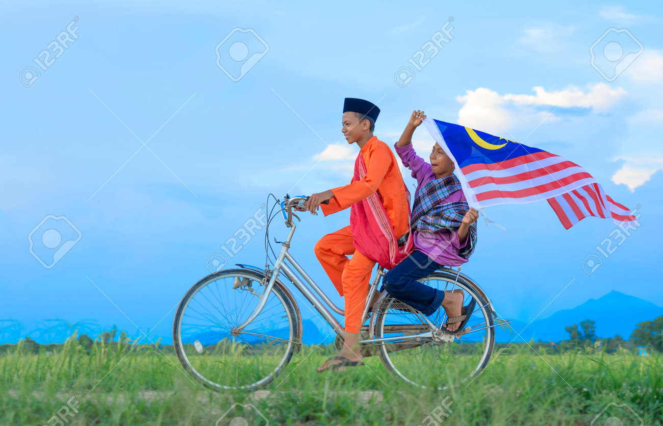 independence Day concept - Two happy young local boy riding old bicycle at paddy field holding a Malaysian flag - 64176941