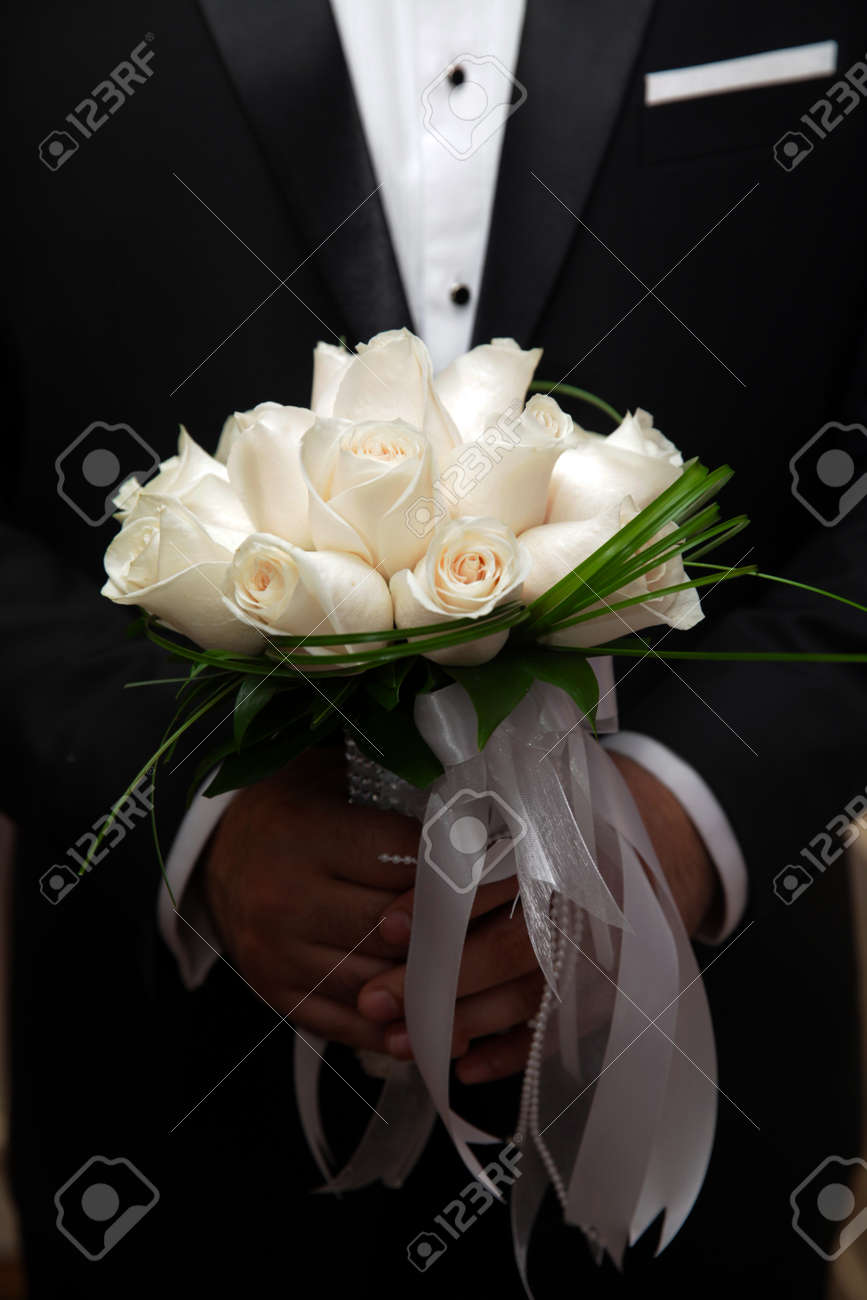 Beautiful Wedding Bouquet Of White Roses In Hands Of Newlyweds Stock