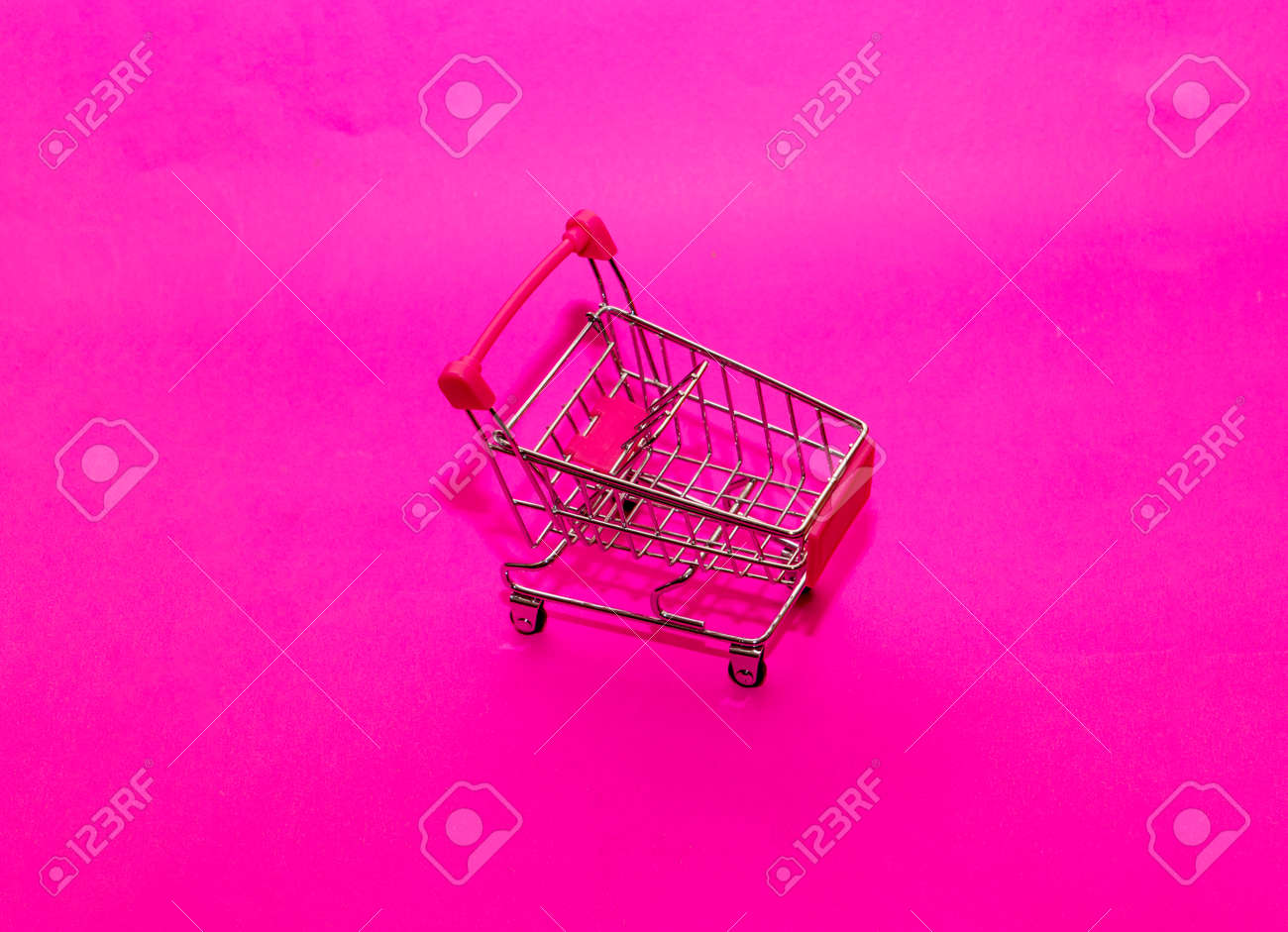 empty shopping cart on pink background. Shopping concept - 141039412
