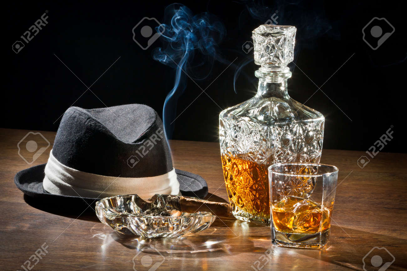 Retro scene, hat, smoking cigar and whisky with carafe - 12583221