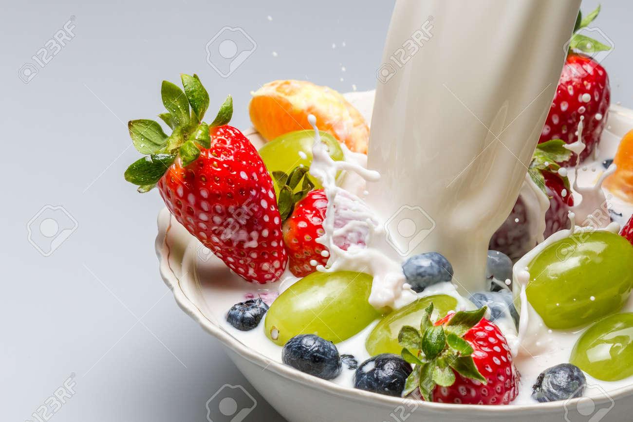 Splash of milk pushes fresh fruit from the bowl Stock Photo - 13138957
