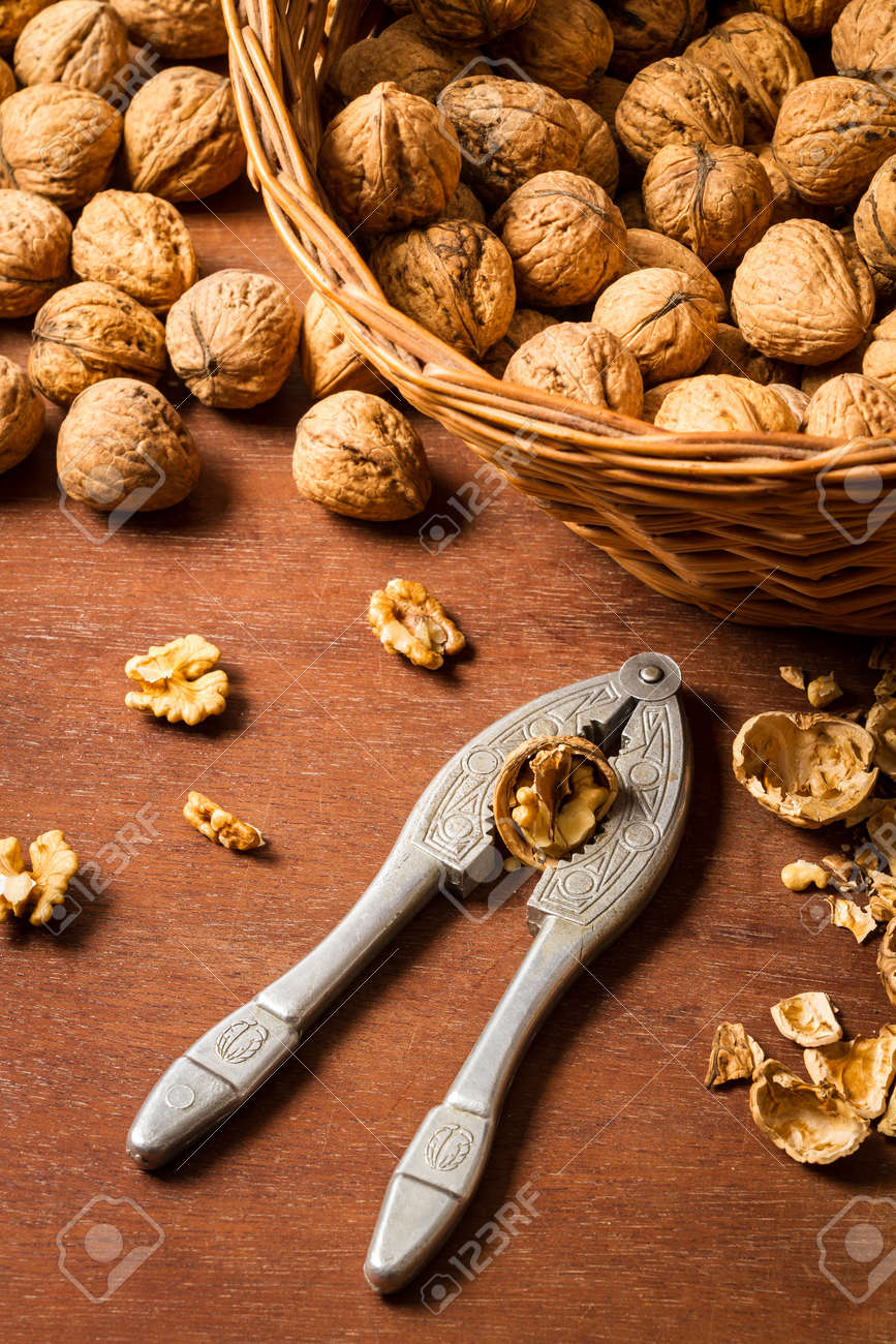 Cracking walnuts on old wooden table Stock Photo - 16397562