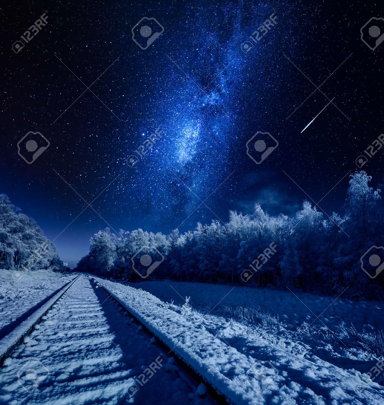 Milky way over frozen railway line in winter at night - 115297796
