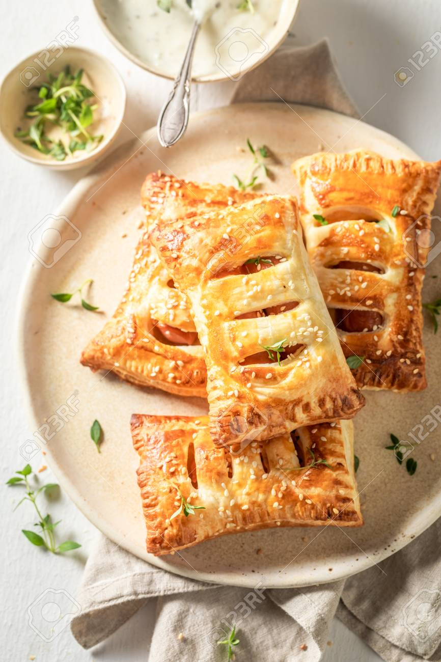 Delicious sausage in puff pastry with thyme and sesame seeds - 121096232