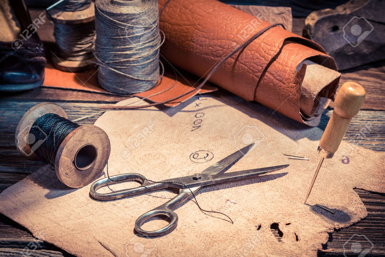 Closeup of vintage cobbler workplace with shoes, laces and tools - 128701723