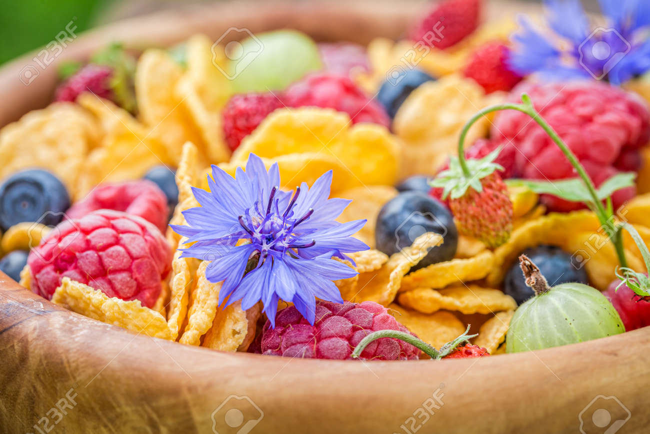 Flowers and fruits with cornflakes. Healthy and slimming breakfast in garden. - 168051113