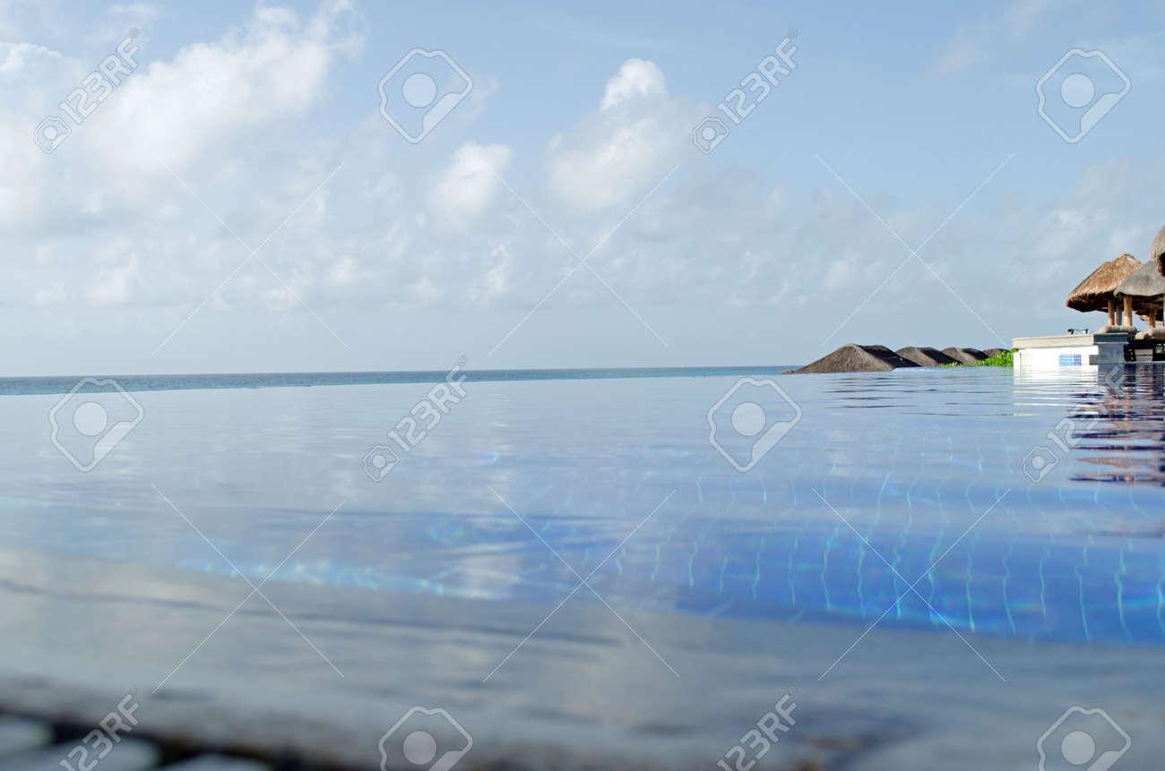 Infinity edge swimming pool. Summer, sand