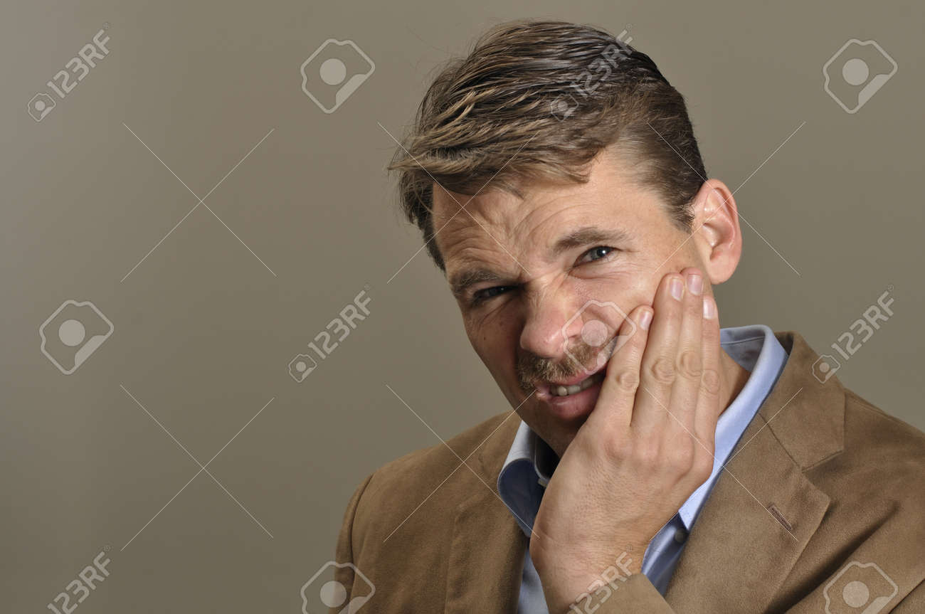 Man with toothache clutches jaw with hand Stock Photo - 11767043