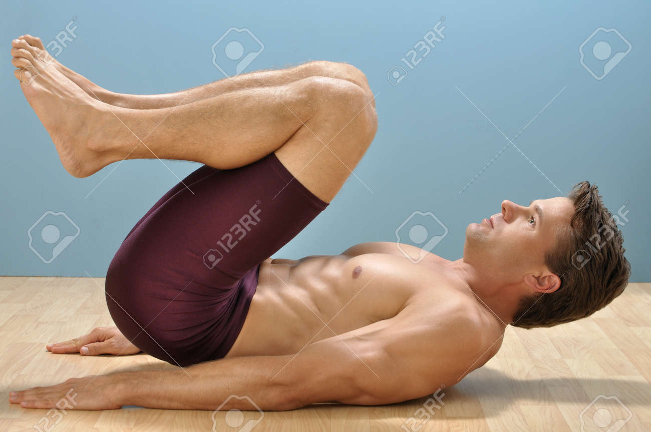 Fit muscular shirtless man performs reverse crunch abdominals exercise on floor Stock Photo - 16648191