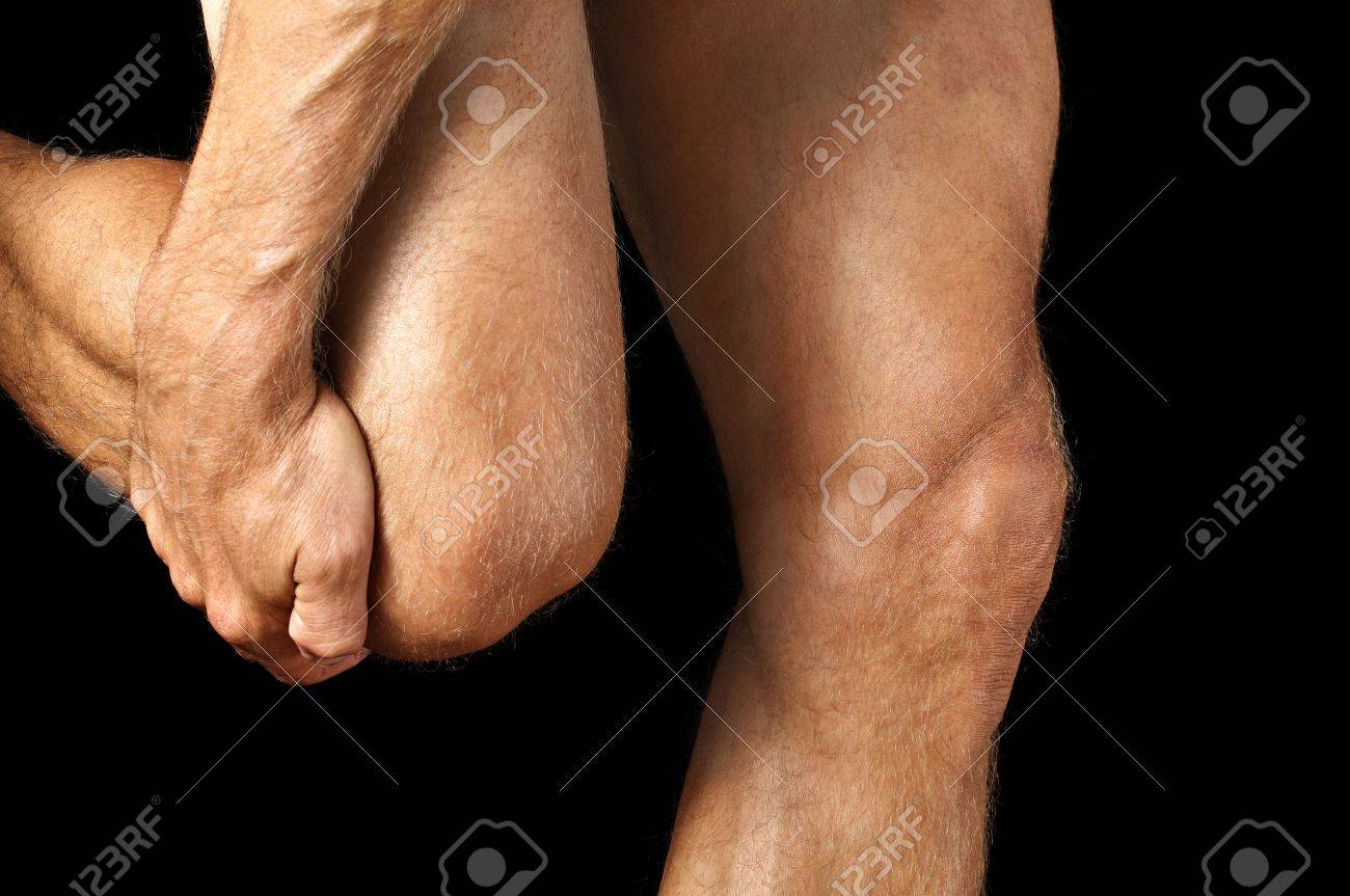 Closeup of man grasping his knee while walking on black background Stock Photo - 17945263