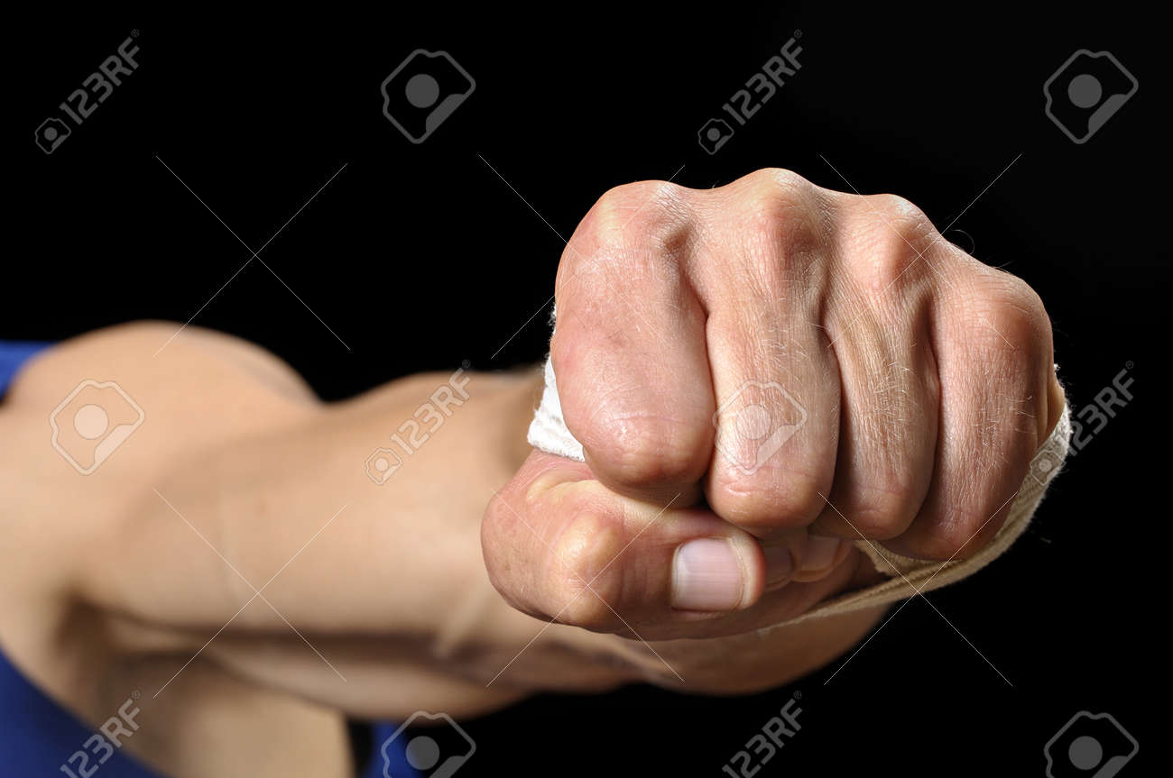 Closeup of muscular man throwing fist at camera on black background Stock Photo - 17945259