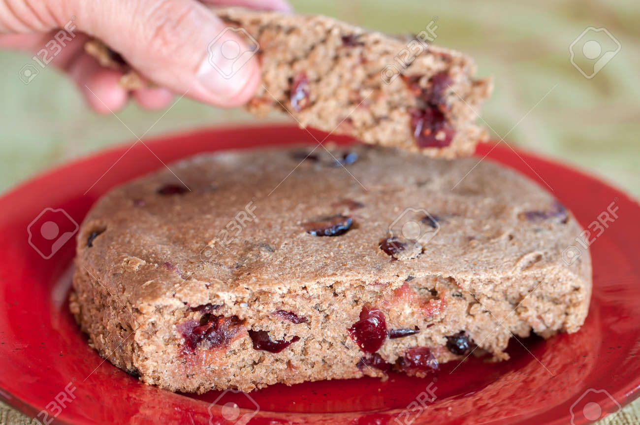 Macro closeup of homemade sourdough bread cake with cranberries and hand of person lifting piece Stock Photo - 24755718