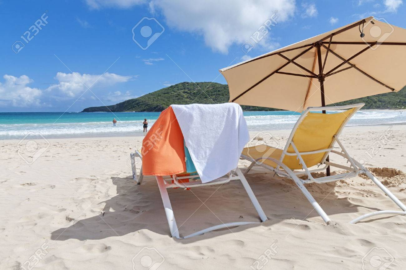 Pastel Colored Lounge Chairs And Umbrella On Fine Sandy Flamenco Beach On  Beautiful Sunny Day On