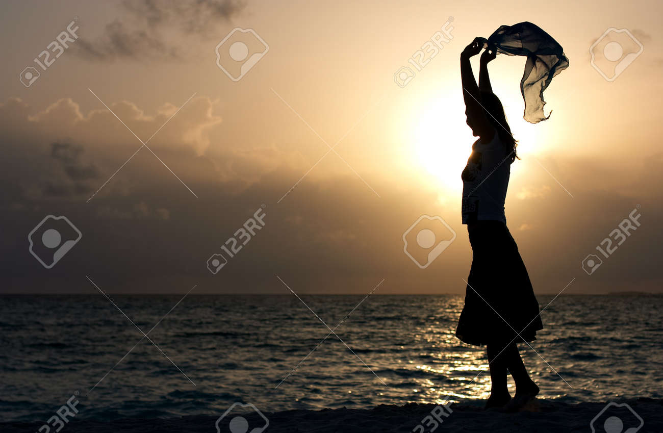 silhouette of young girl dancing on the beach at sunset Stock Photo - 1415078