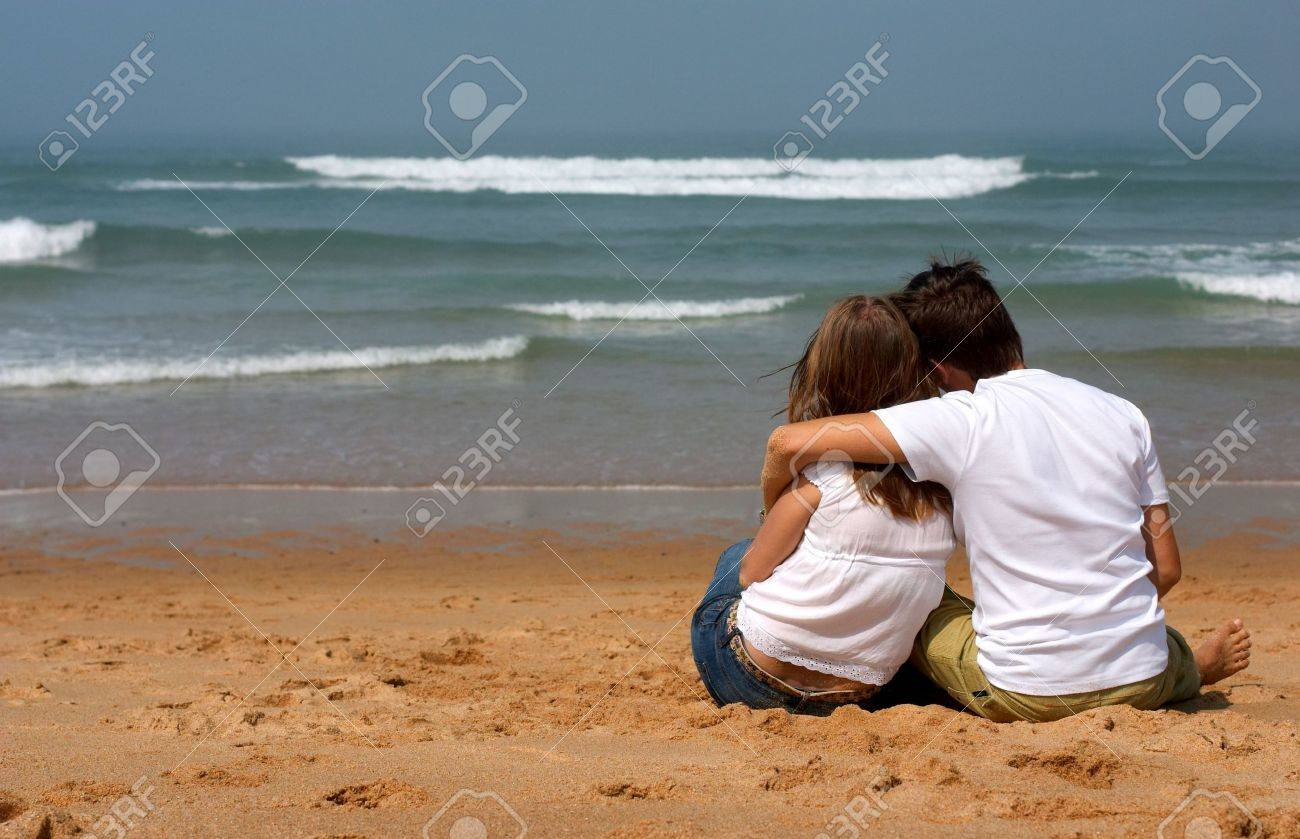 Romantic young couple in casual clothes sitting on the sandy beach and looking to ocean Stock Photo - 1908719