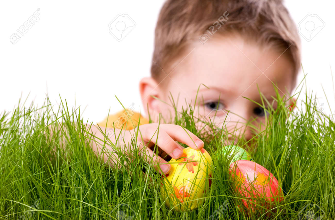Easter egg hunt. Cute boy searching for easter eggs hidden in fresh green grass. Isolated on white background Stock Photo - 2587828