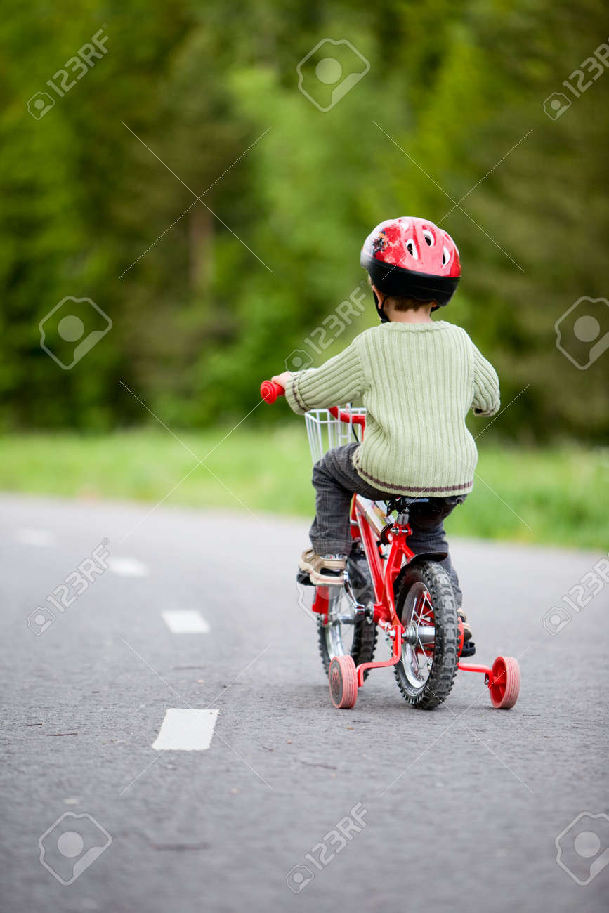 3 years old boy wearing safety bicycle helmet riding a bike Stock Photo - 3224905