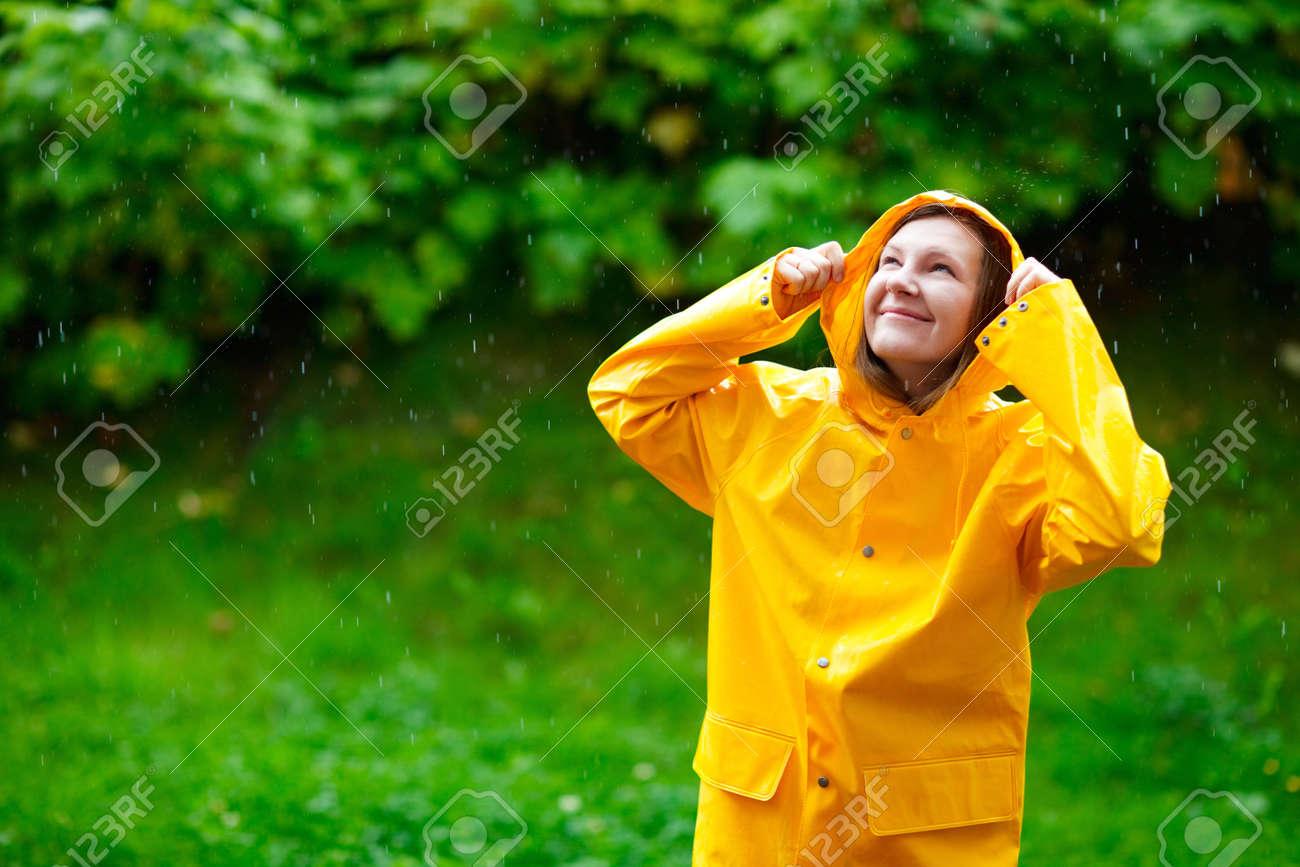 Happy young woman in yellow raincoat under rain Stock Photo - 5528490
