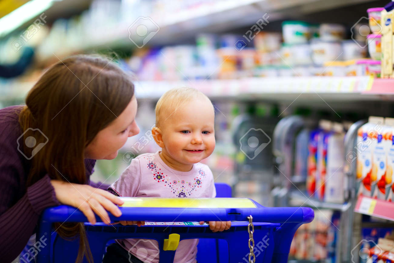 Young mother with baby daughter shopping in supermarket Stock Photo - 5528472
