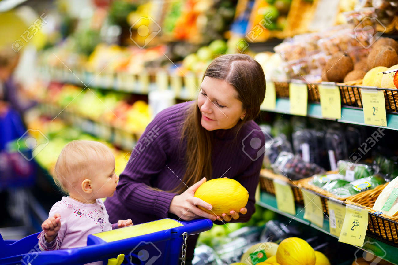 Young mother with baby daughter shopping in supermarket Stock Photo - 5559265
