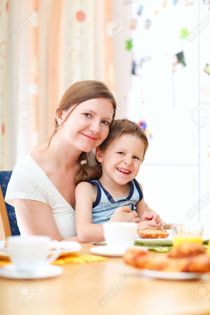 Young happy mother and son having breakfast together Stock Photo - 5604673