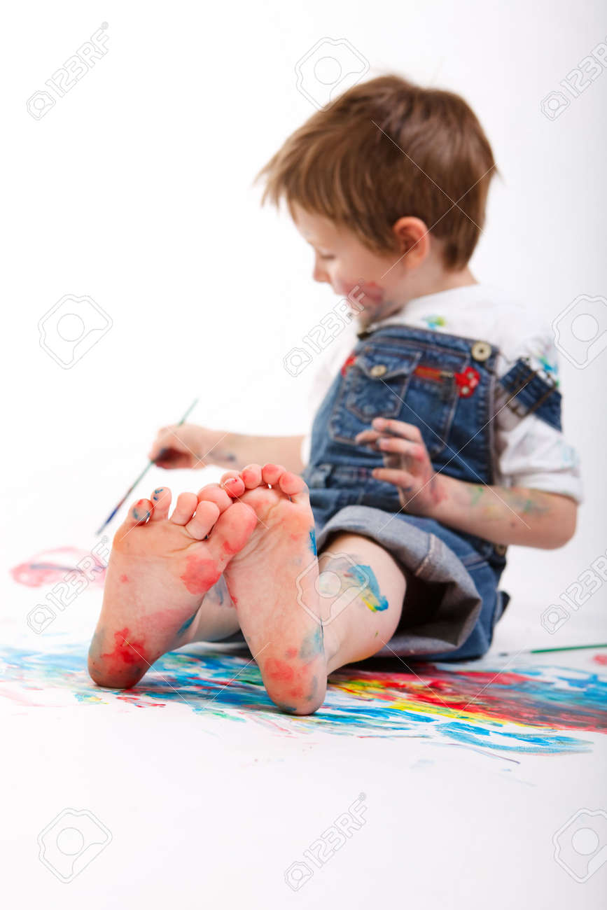 Funny photo of cute 5 years old boy painting on white background. Focus on feet. Stock Photo - 5774475