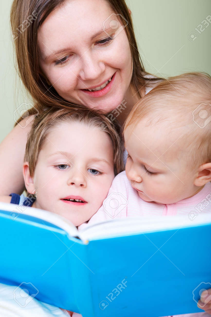 Young mother with her two kids reading book in bed Stock Photo - 5774488