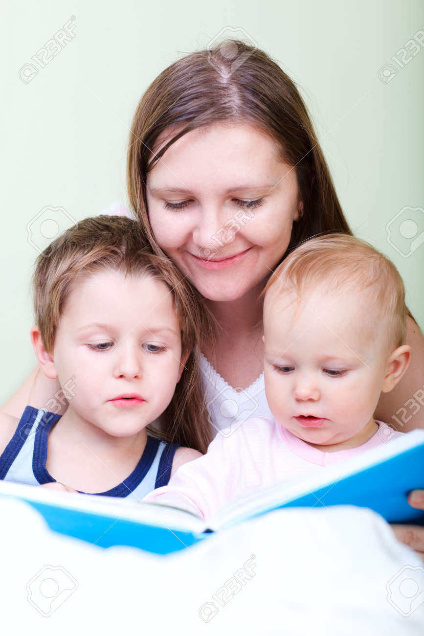 Young mother with her two kids reading book in bed Stock Photo - 5938481