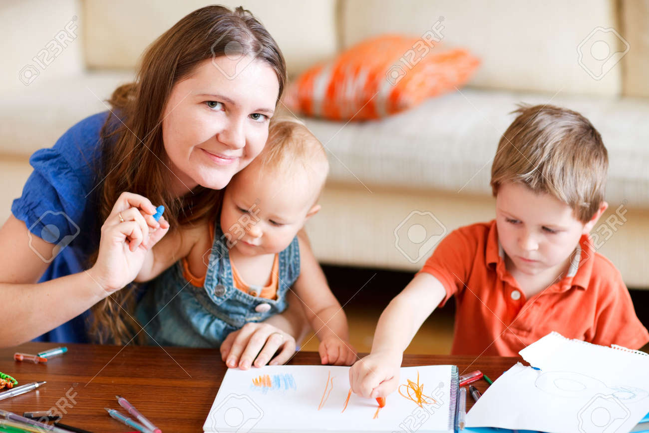 Young mother and her two kids drawing together. Can be used also in kindergarten/daycare context Stock Photo - 6276162