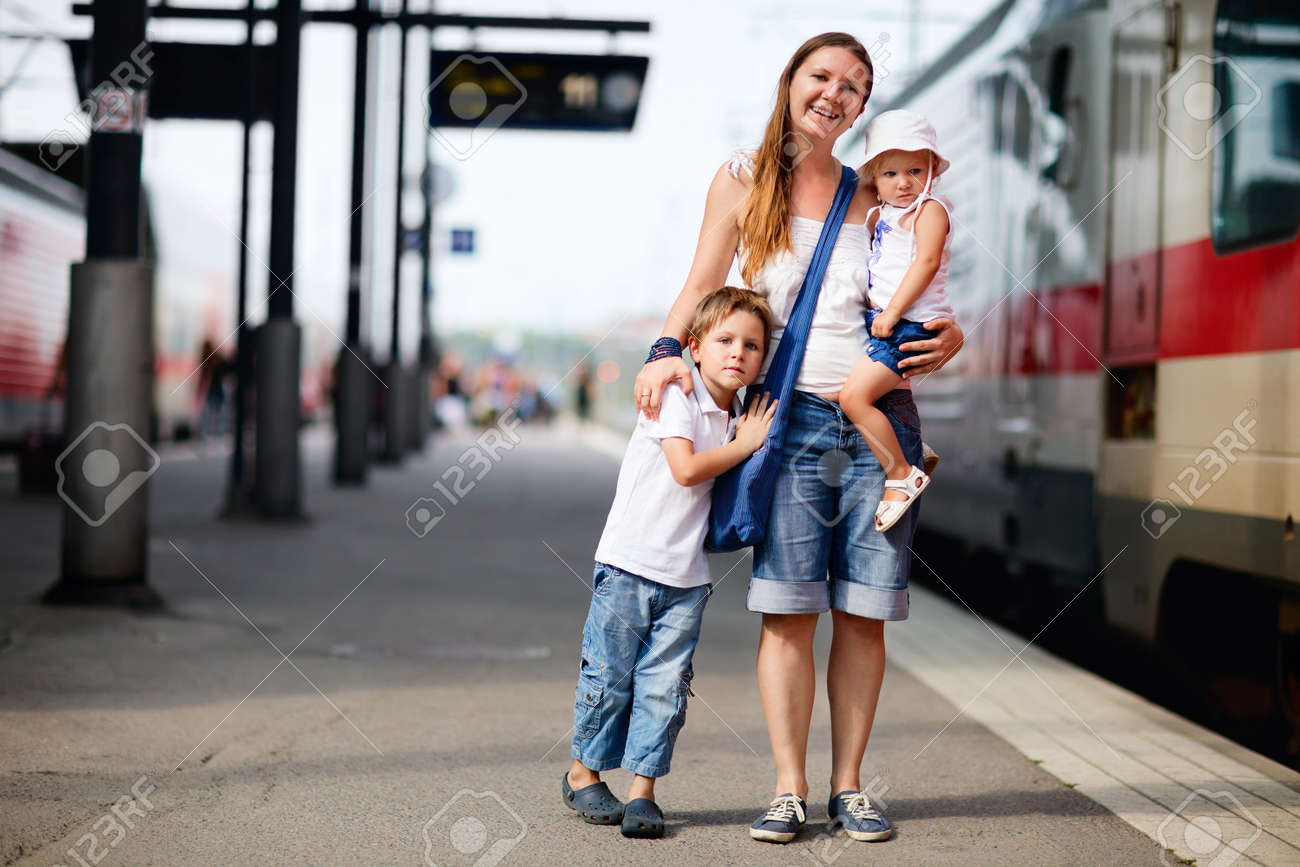 Young mother and two kids waiting for train on railway station platform Stock Photo - 7639855