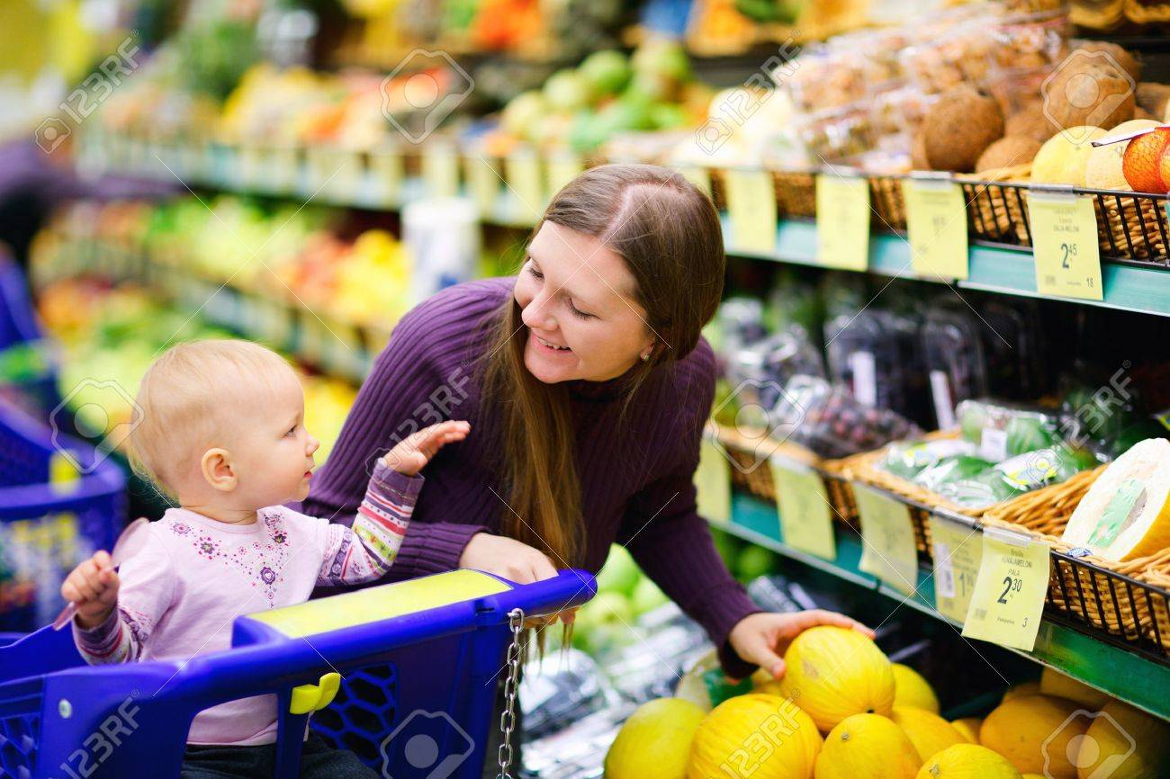 Young mother and her adorable baby daughter selecting fruits in supermarket Stock Photo - 7705998
