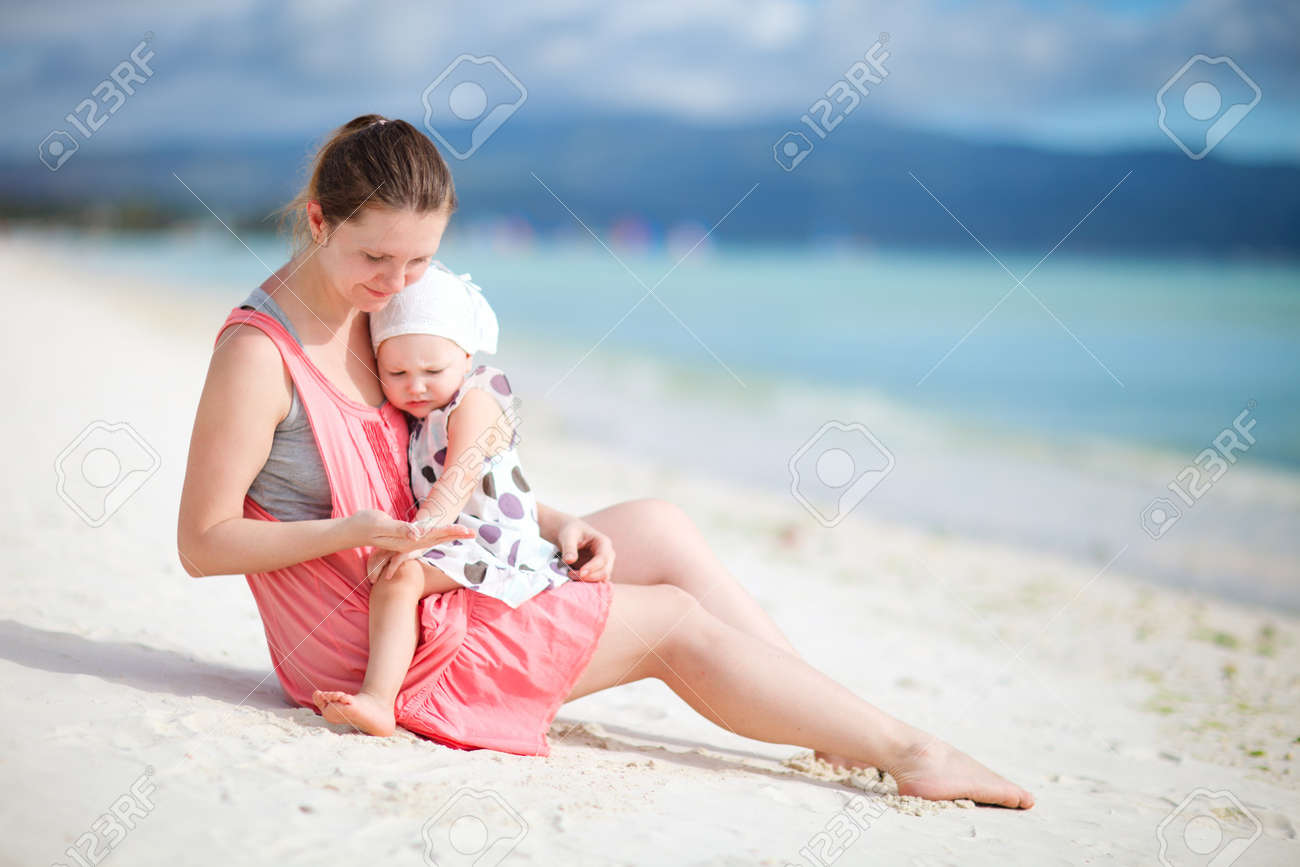 Young mother and her little daughter sitting on tropical beach Stock Photo - 7706013