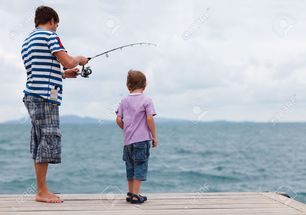 Young father and his son fishing together from wooden jetty Stock Photo - 7819170