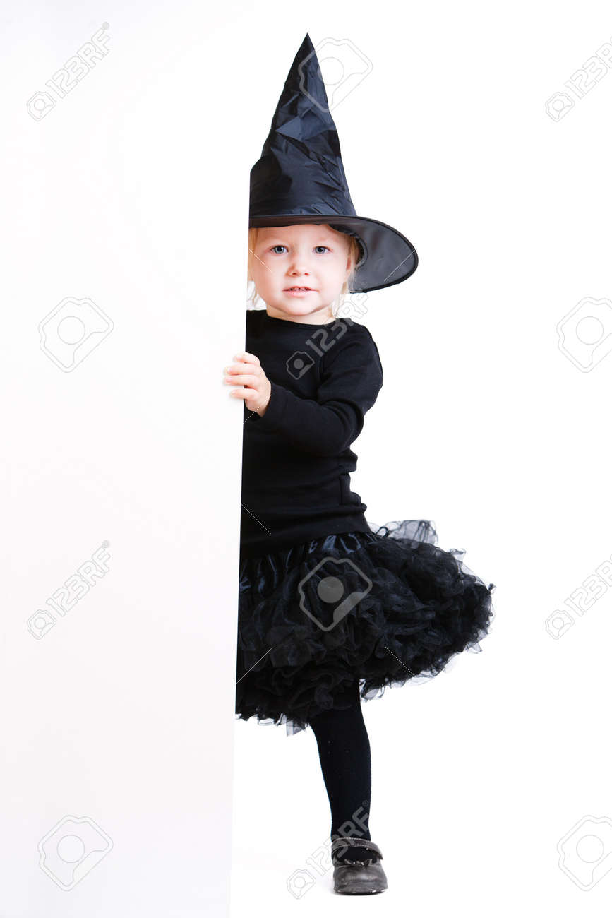 Playful Little Girl Dresses For Halloween In Witch Costume Hiding ...