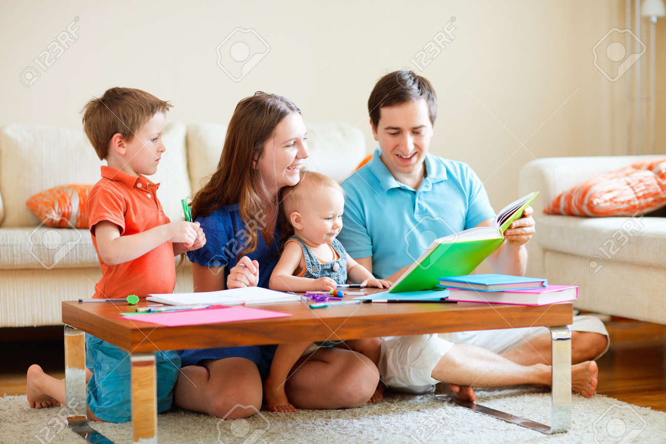 Family of four reading and drawing together at home Stock Photo - 8061127