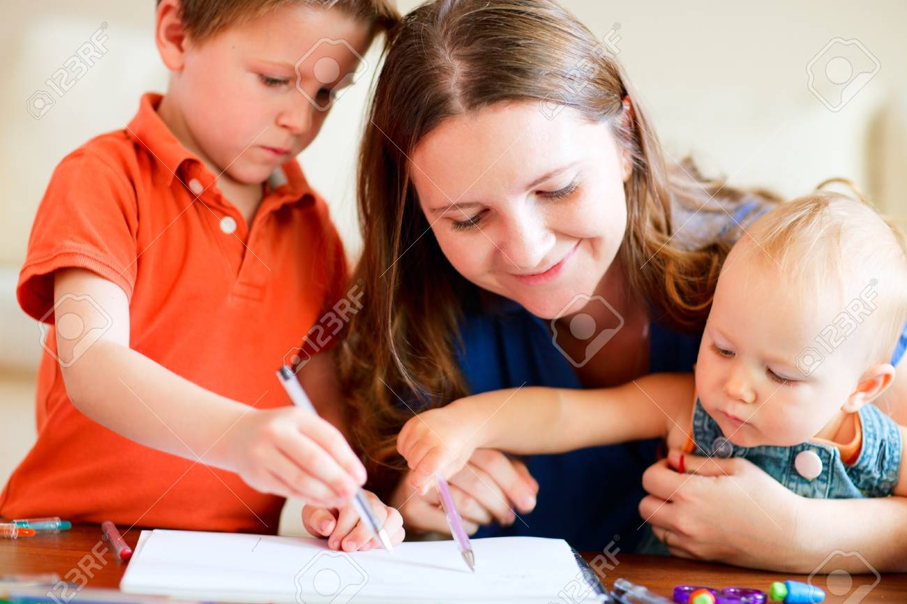 Young mother and her two kids drawing together Stock Photo - 8061117
