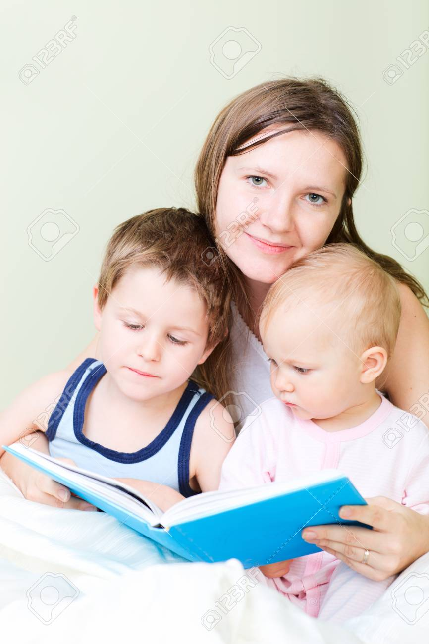 Young mother with her two kids reading book in bed Stock Photo - 8221973