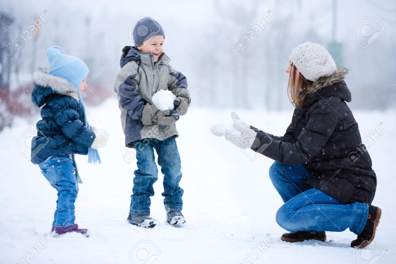 Mother and two kids having fun outdoors on beautiful winter day Stock Photo - 8355126