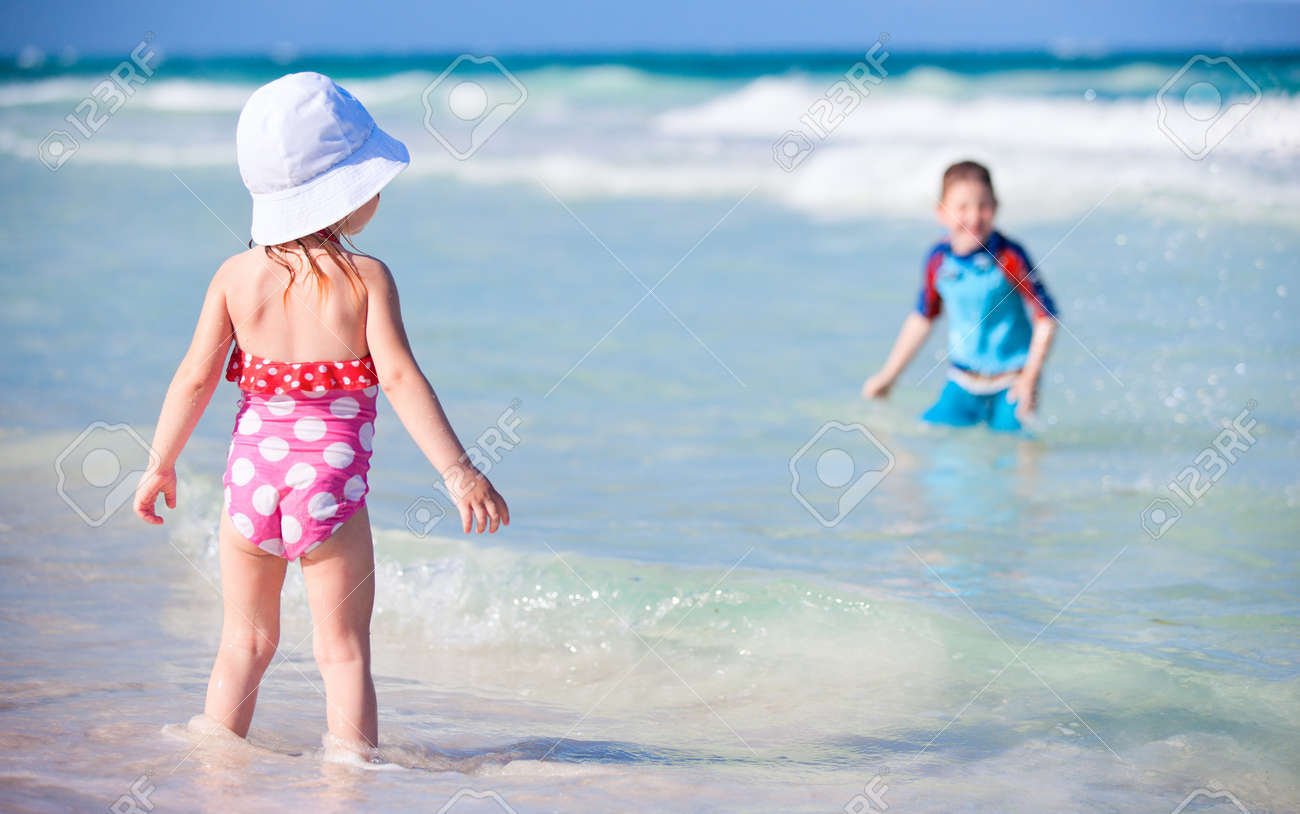 Two kids playing in water at Caribbean coast in Mexico Stock Photo - 9784294