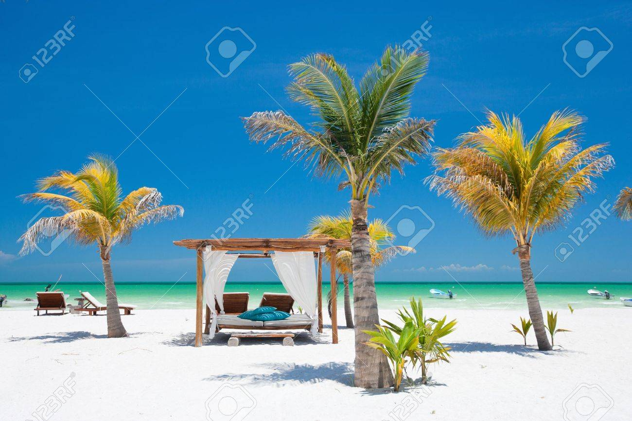 179d12946f6fb Beach beds among palm trees at perfect tropical coast Stock Photo - 9784309