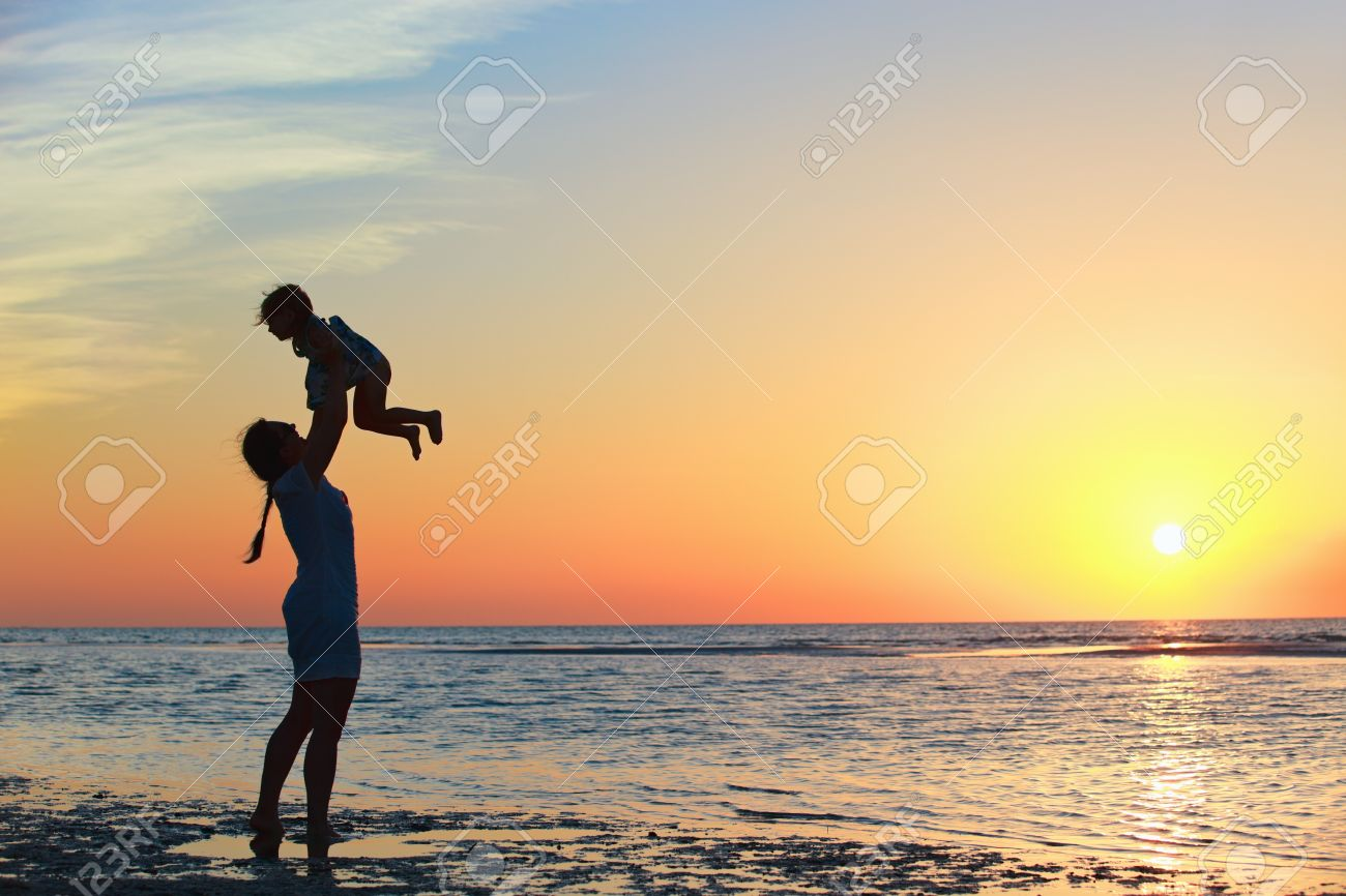 Mother and little daughter silhouettes on beach at sunset - 9862599