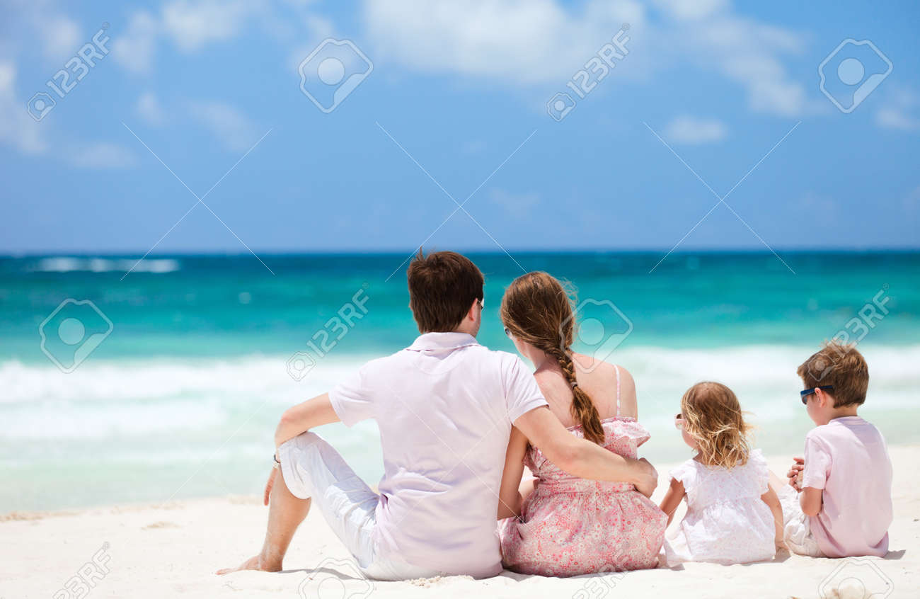 Family of four sitting on Caribbean beach Stock Photo - 10200852