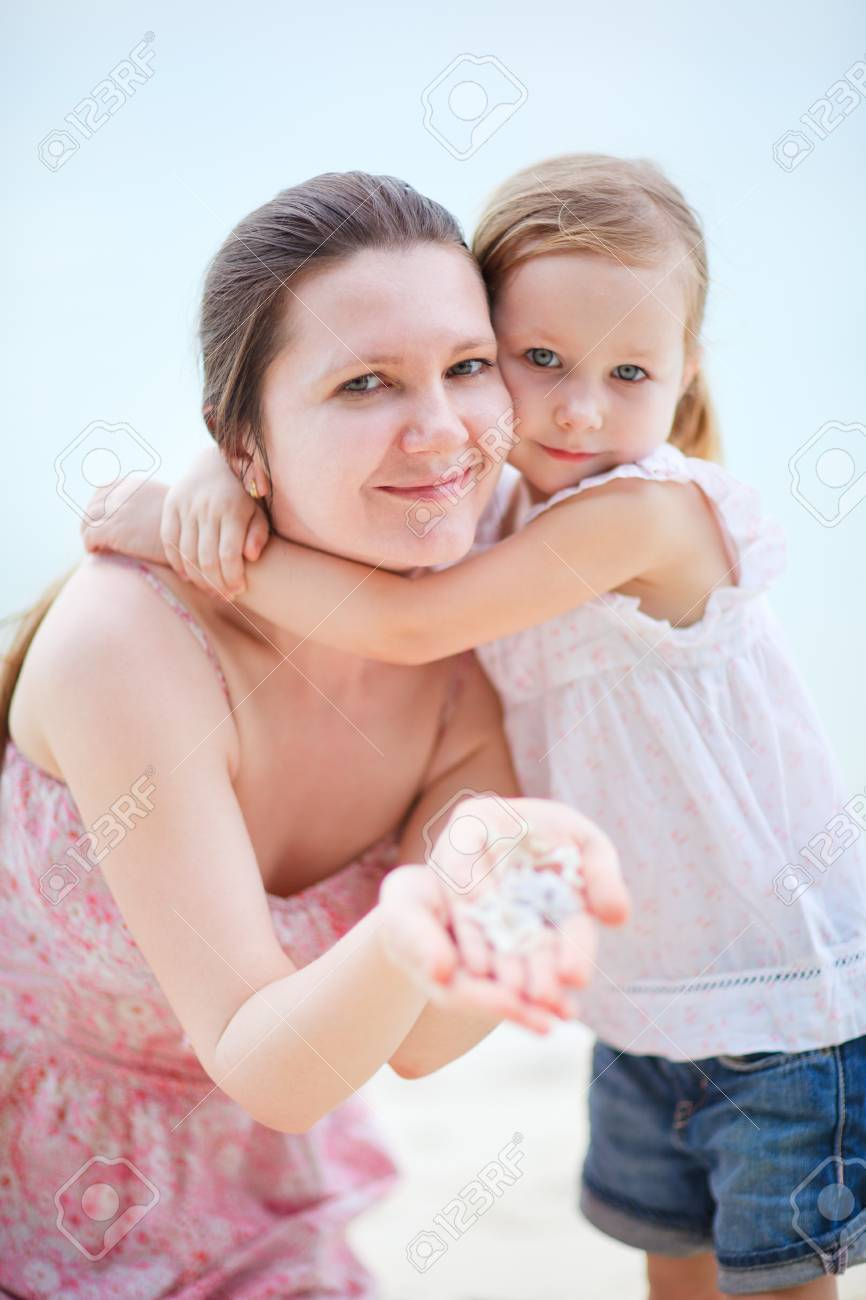 Young mother and her adorable little daughter with seashells Stock Photo - 12981721