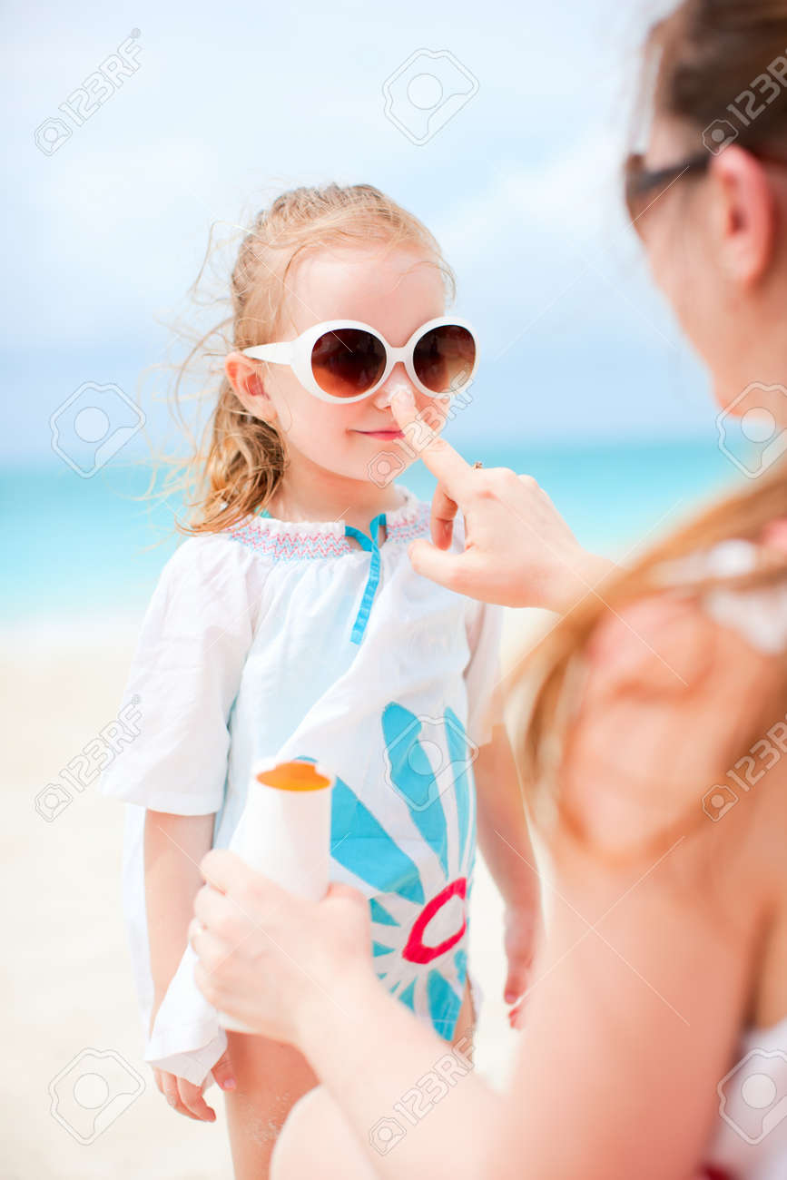 Mother applying sunblock cream on her daughters nose Stock Photo - 13653347